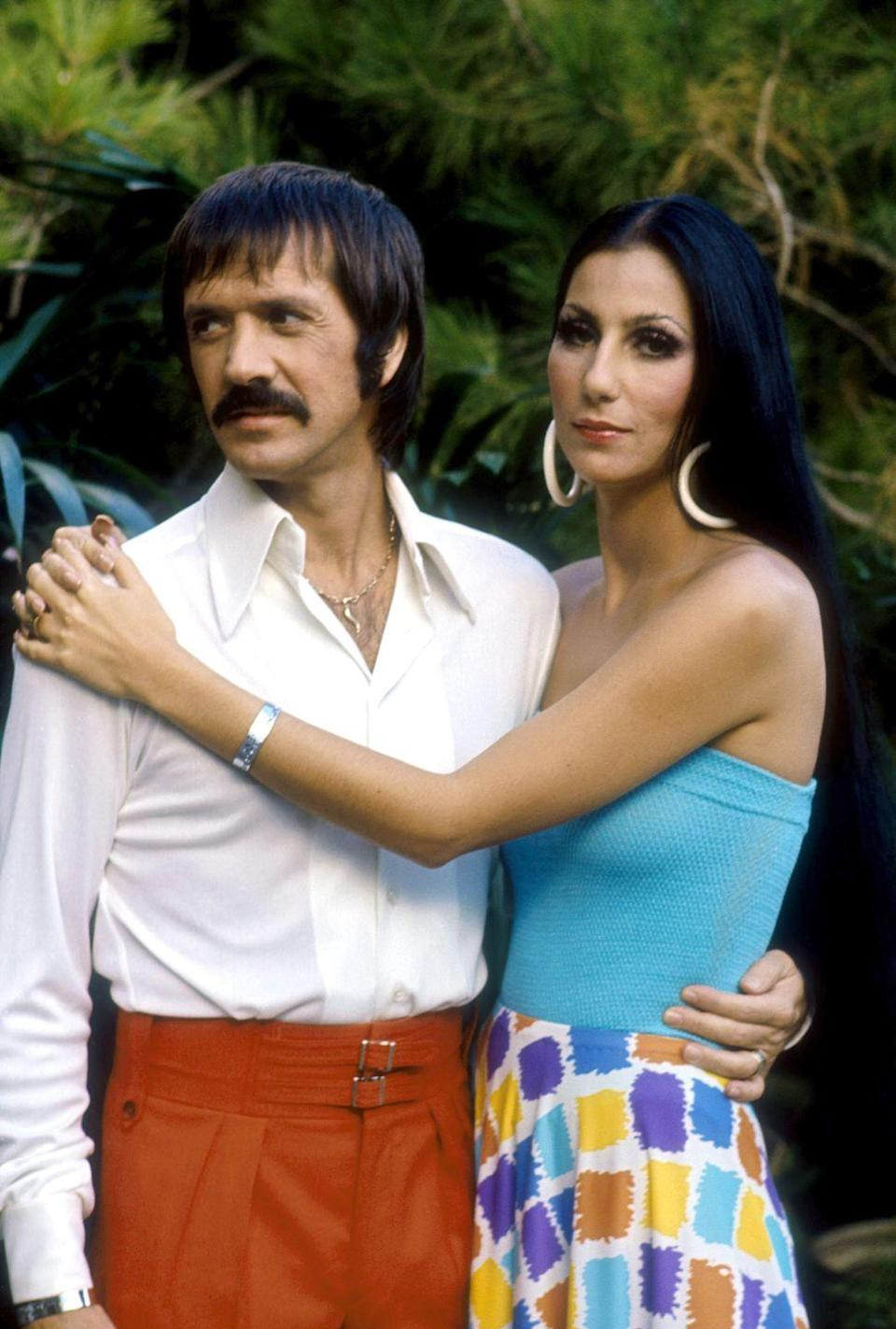 <p>Wearing white hoop earrings, a blue tube top, and printed skirt in a promotional photo for <em>The Sonny and Cher Show</em>.</p>