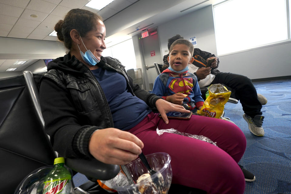 Celestina Ramirez, left, a migrant from Honduras, talks with her son Yancarlos Amaya, 5, before boarding a plane at Valley International Airport, Wednesday, March 24, 2021, in Harlingen, Texas. The mother and son, who are headed to Baltimore to reunite with Ramirez's brother, were allowed to stay in the U.S. after turning themselves in to U.S. Customs and Border Protection upon crossing the border. (AP Photo/Julio Cortez)