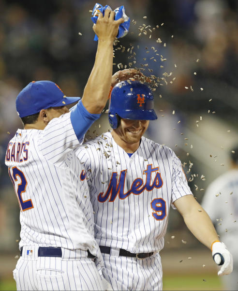 New York Mets' Juan Lagares (12) showers Brandon Nimmo with sunflower seeds after Nimmo drew a bases-loaded walk to drive in the winning run in the Mets' 5-4 victory over the Miami Marlins in 11 innings in a baseball game Tuesday, Sept. 24, 2019, in New York. (AP Photo/Kathy Willens)