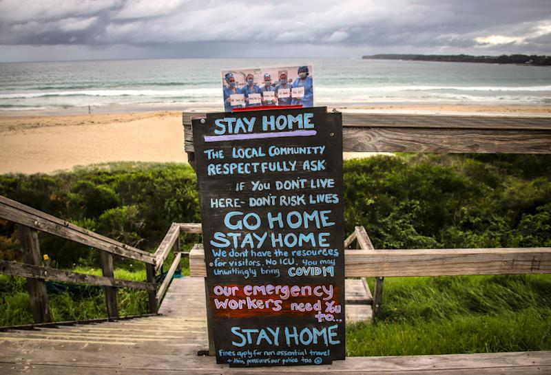 A sign asking people to not travel due to the coronavirus stands at a stairway leading onto Mollymook Beach. Source: Getty