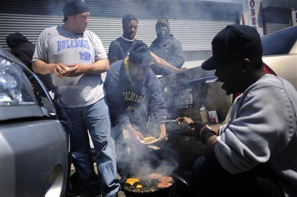 Job seekers grill hamburgers as they wait in front of the training offices of Local Union 46, the union representing metallic lathers and reinforcing ironworkers, in the Queens borough of New York, April 29, 2012.