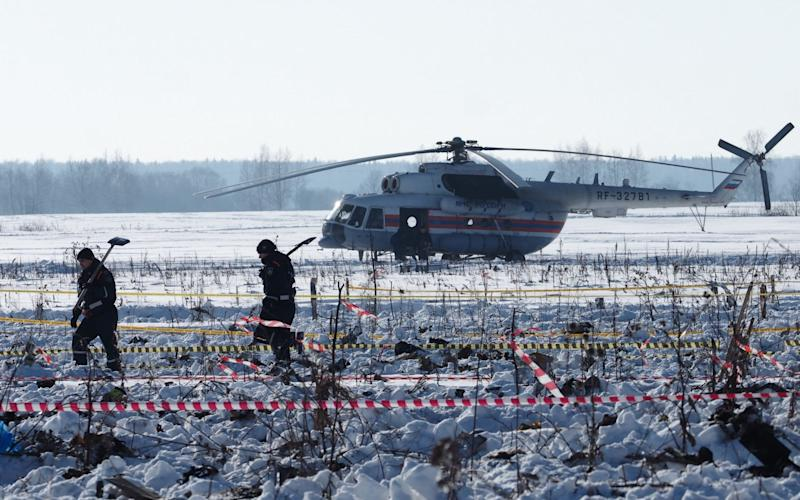Emergencies ministry workers at the crash site on Monday - TASS