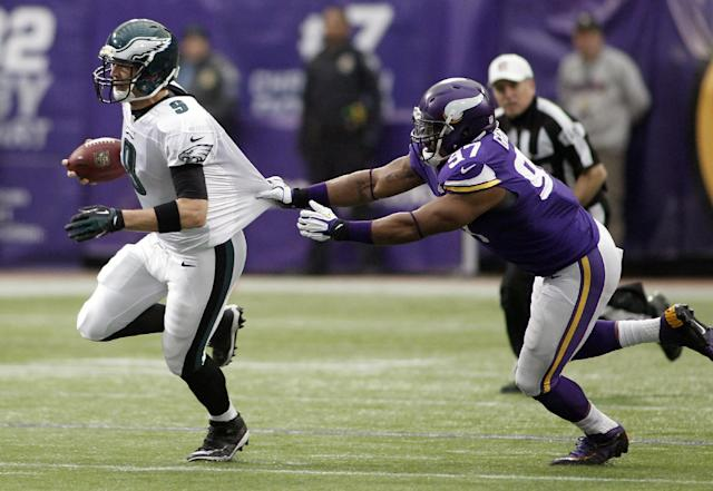 Philadelphia Eagles quarterback Nick Foles, left, runs from Minnesota Vikings defensive end Everson Griffen during the first half of an NFL football game, Sunday, Dec. 15, 2013, in Minneapolis. (AP Photo/Andy King)