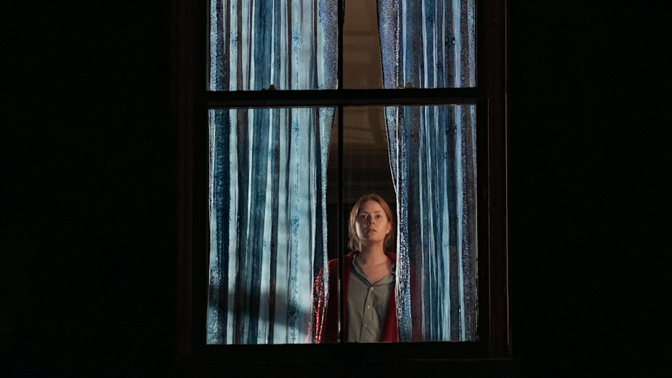 Amy Adams glares out a window in The Woman in the Window.