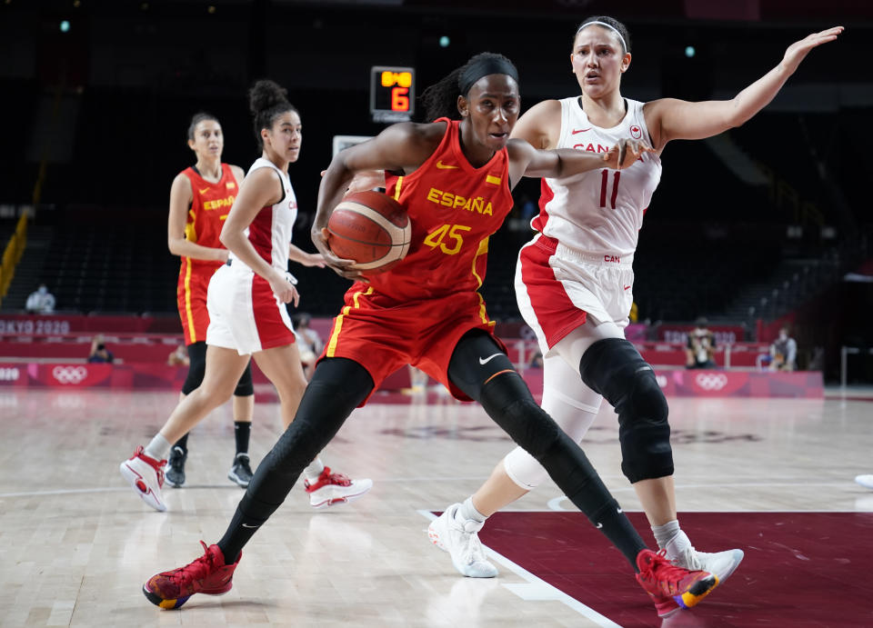 Spain's Astou Ndour (45), is fouled by Canada's Natalie Achonwa (11) during women's basketball preliminary round game at the 2020 Summer Olympics, Sunday, Aug. 1, 2021, in Saitama, Japan. (AP Photo/Charlie Neibergall)