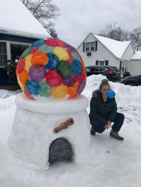 PHOTO: Katina Gustafson of East Providence, Rhode Island, has been handcrafting multi-dimensional snow designs since 2009. Here she kneels with a gumball machine she created from snow in March 2019. (Katina Gustafson)
