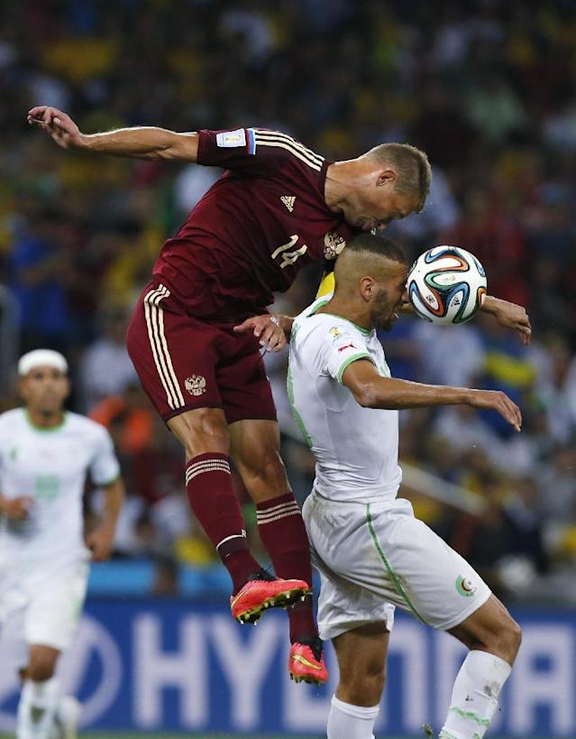 Russia's Vasily Berezutsky and Algeria's Islam Slimani go for a header during the group H World Cup soccer match between Algeria and Russia at the Arena da Baixada in Curitiba, Brazil, Thursday, June 26, 2014. (AP Photo/Jon Super)