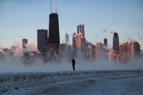 A man walks along an ice-covered break-wall along Lake Michigan while temperatures were hovering around -20F (-29C) on 31 January, 2019 in Chicago, Illinois. (Photo by Scott Olson/Getty Images)