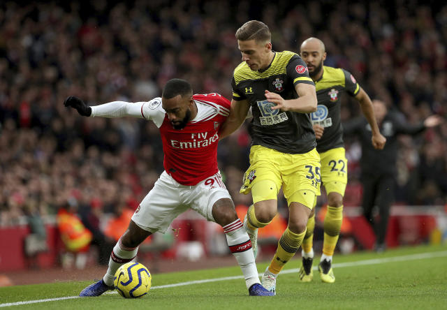 Arsenal's Alexandre Lacazette, left and Southampton's Jan Bednarek battle for the ball during the English Premier League soccer match between Arsenal and Southampton, at the Emirates Stadium, in London, Saturday, Nov. 23, 2019. (Yui Mok/PA via AP)