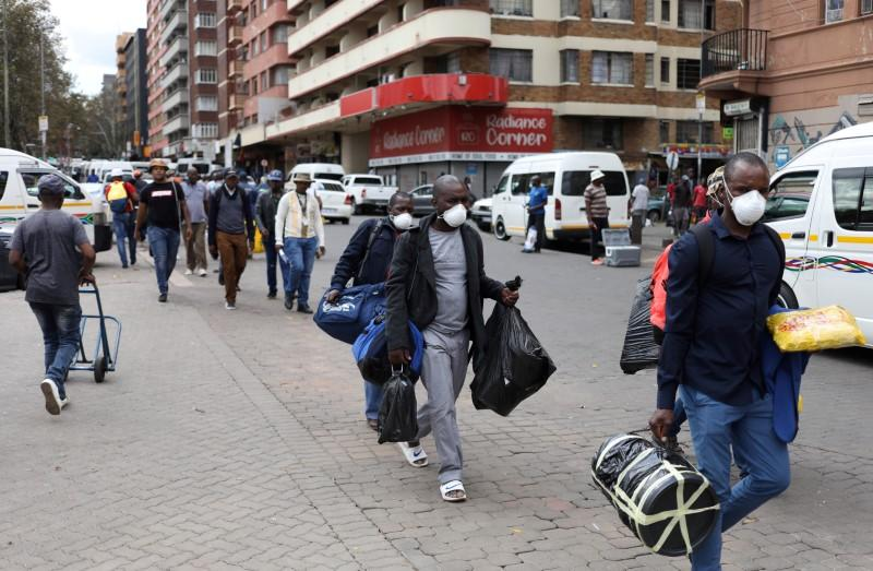 Passengers wearing masks walk to a taxi rank as residents of a number of African cities where the coronavirus is spreading are heading to the countryside to try to escape from the disease, in Johannesburg