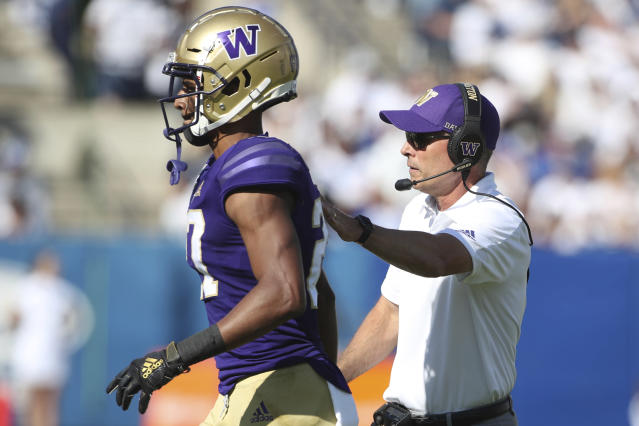 Washington head coach Chris Petersen, (L), congratulates defensive back Keith Taylor (27) during the second half of an NCAA college football game, against BYU Saturday, Sept. 21, 2019, in Provo, Utah.(AP Photo/George Frey)