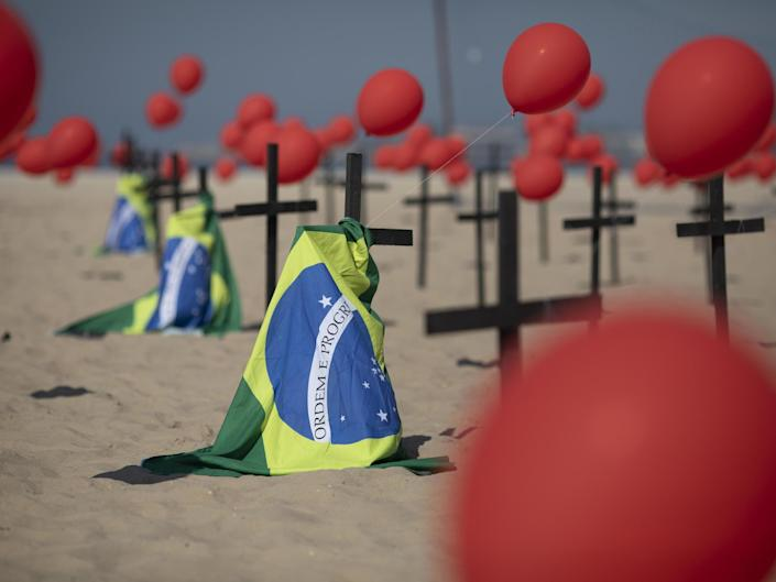 Crosses, red balloons and Brazilian nation flags are placed in the sand on Copacabana beach in a demonstration organised by Rio de Paz: AP Photo/Silvia Izquierdo