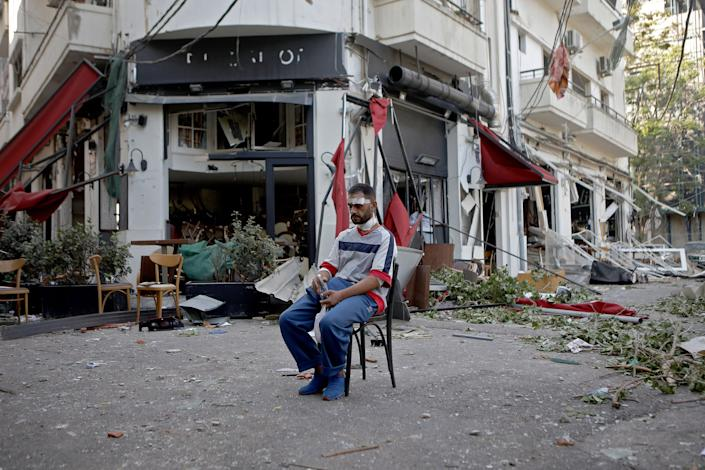 An injured man sits next to a restaurant in the Mar Mikhael neighborhood of Beirut on August 5 in the aftermath of the massive explosion.   Patrick Baz—AFP via Getty Images