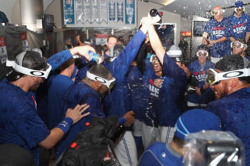The Toronto Blue Jays celebrate in the clubhouse after defeating the Baltimore Orioles 5-2 in the eleventh inning to win the American League Wild Card game (AFP Photo/Tom Szczerbowski)