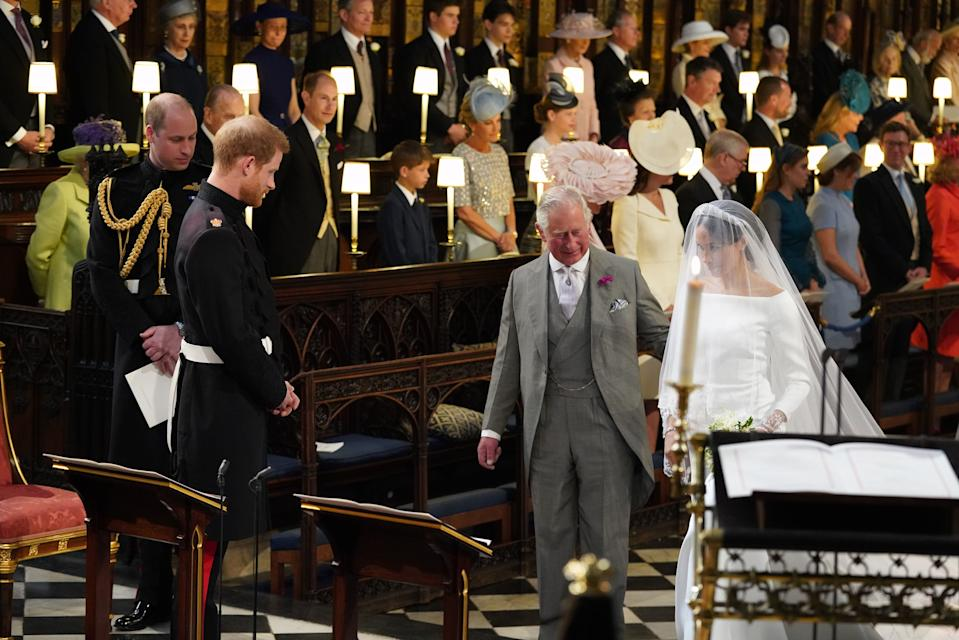 TOPSHOT - Britain's Prince Harry, Duke of Sussex (2nd L), looks at his bride, Meghan Markle, as she arrives accompanied by the Britain's Prince Charles, Prince of Wales in St George's Chapel during the wedding ceremony of Britain's Prince Harry, Duke of Sussex and US actress Meghan Markle in St George's Chapel, Windsor Castle, in Windsor, on May 19, 2018. (Photo by Jonathan Brady / POOL / AFP)        (Photo credit should read JONATHAN BRADY/AFP via Getty Images)