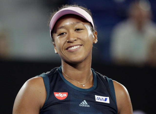 Japan's Naomi Osaka smiles during her first round match against Poland's Magda Linette at the Australian Open tennis championships in Melbourne, Australia, Tuesday, Jan. 15, 2019. (AP Photo/Kin Cheung)