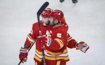 Calgary Flames' Mark Giordano, right, celebrates his goal with teammate Sam Bennett during third-period NHL hockey game action against the Vancouver Canucks in Calgary, Alberta, Monday, Jan. 18, 2021. (Jeff McIntosh/The Canadian Press via AP)