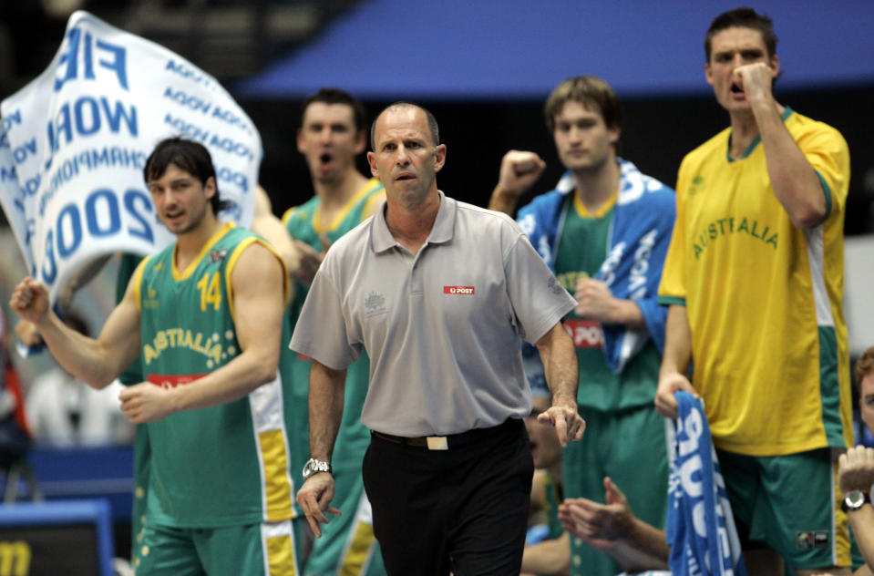 FILE - In this Aug. 27, 2006, file photo, Australia's head coach Brian Goorjian, center, and players watch early action against USA Sunday, Aug. 27, 2006, at the world basketball championship in Saitama, Japan. Goorjian will take the Australians men's basketball team to a third Olympics after he was named new head coach of the Boomers on Friday, Nov. 13, 2020. (AP Photo/Dusan Vranic, File)