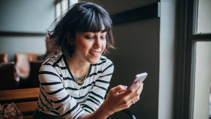 Happy woman using phone at cafe.
