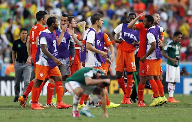 Dutch players celebrate after the World Cup round of 16 soccer match between the Netherlands and Mexico at the Arena Castelao in Fortaleza, Brazil, Sunday, June 29, 2014. The Netherlands won the match 2-1. (AP Photo/Wong Maye-E)