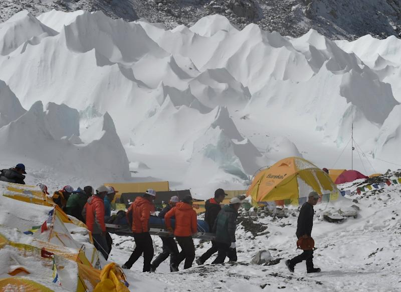 Rescue team personnel carry an injured person towards a waiting rescue helicopter at Everest Base Camp on April 26, 2015, a day after an avalanche triggered by an earthquake devastated the camp (AFP Photo/Roberto Schmidt)