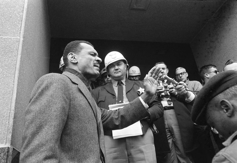 FILE - In this Feb. 5, 1965 file photo, C.T. Vivian, left, leads a prayer on the courthouse steps in Selma, Ala., after Sheriff James Clark, background with helmet, stopped him at the door with a court order. Vivian led hundreds of demonstrators carrying petitions asking longer voter registration hours. Vivian, a civil rights veteran who worked alongside the Rev. Martin Luther King Jr. and served as head of the organization co-founded by the civil rights icon, died at home in Atlanta of natural causes Friday, July 17, 2020, his friend and business partner Don Rivers confirmed to The Associated Press. Vivian was 95. (AP Photo/Horace Cort)