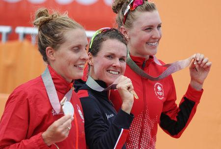 Triathlon - Gold Coast 2018 Commonwealth Games - Women's Final - Southport Broadwater Parklands - Gold Coast, Australia - April 5, 2018 - Gold medallist Flora Duffy of Bermuda, silver medallist Jessica Learmonth of England and bronze medallist Joanna Brown of Canada. REUTERS/Athit Perawongmetha
