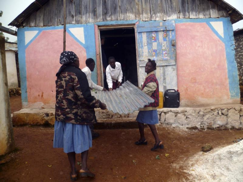This July 3, 2011 photo shows villagers as they help unload building supplies that will be used for new wooden houses in Maplat, Haiti. Dozens of villagers came throughout the week to help Farsight Christian Mission with the building process, sometimes showing up before dawn. Levern Halstead, who runs Farsight Christian Mission from his home outside Chattanooga, Tenn., says that his trips must have an objectively measurable result _ a new building, a new bridge, a new well.     (AP Photo/Christina Rexrode)