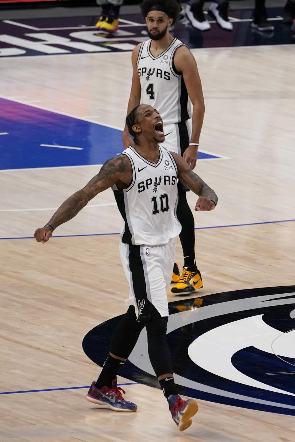 San Antonio Spurs forward DeMar DeRozan (10) celebrates after sinking a basket in the final second of the second half of an NBA basketball game against the Dallas Mavericks in Dallas, Sunday, April 11, 2021. Spurs' Derrick White (4) looks on as DeRozan celebrates. (AP Photo/Tony Gutierrez)