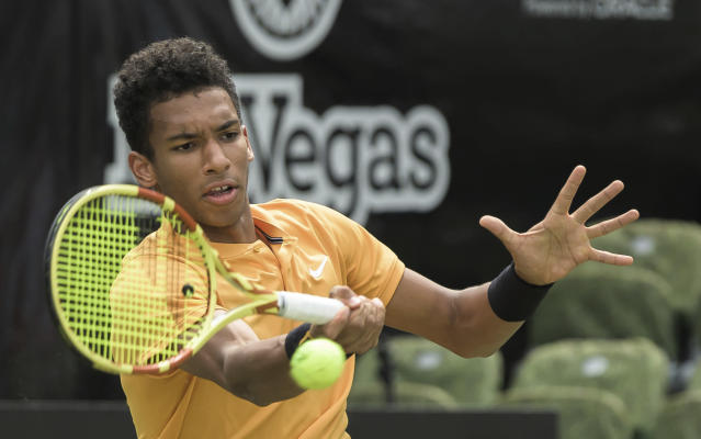 Felix Auger-Aliassime, of Canada, returns a shot to Dustin Brown of Germany, during the quarterfinals of the Stuttgart Open tennis tournament, Friday, June 14, 2019, in Stuttgart, Germany. Auger-Aliassime won 7-6 (3), 6-7 (2), 7-6 (2). (Silas Stein/dpa via AP)