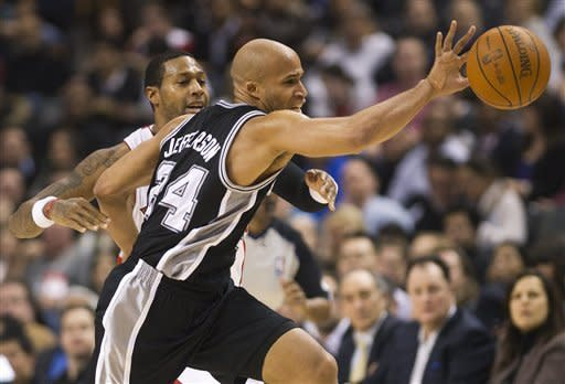 Toronto Raptors forward James Johnson, left, battles for the ball against San Antonio Spurs forward Richard Jefferson during first-half NBA basketball game action in Toronto on Wednesday, Feb. 15, 2012. (AP Photo/The Canadian Press, Nathan Denette)