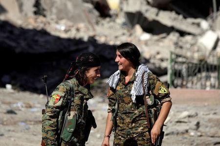 Female fighters from Syrian Democratic Forces (SDF) react in Raqqa