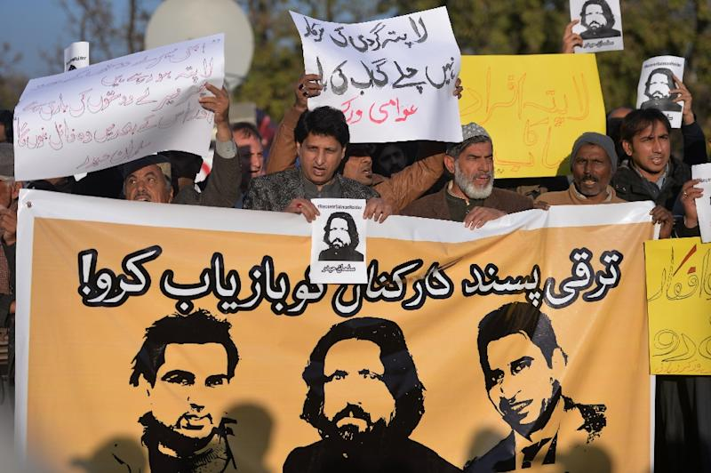 Pakistani human rights activists hold images of bloggers who have gone missing during a protest rally in Islamabad, on January 10, 2017