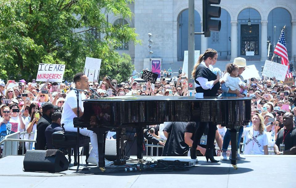 <p>The whole Teigen-Legend family attended the 'Families Belong Together' march and rally in LA to protest against the Trump administration's detention of children and separation of families at the US-Mexico border. </p><p>Legend played the piano while Teigen addressed the crowd, cradling her son Miles. Her mother Pepper, carried her daughter Luna out on stage too.</p>