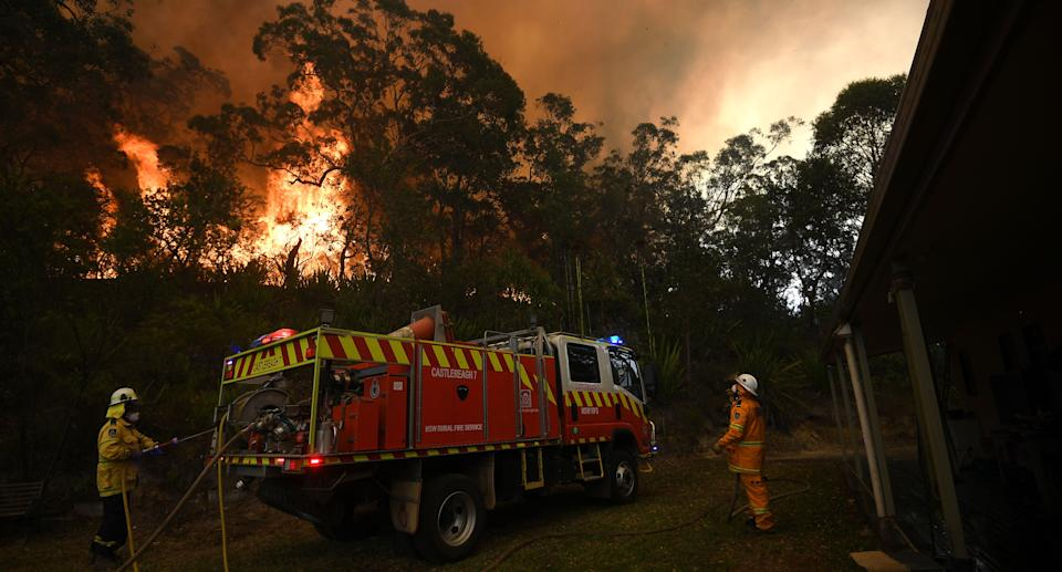 NSW Rural Fire Service and Fire and Rescue NSW crews work to protect a property on Kyola Road in Kulnura as the Wrights Creek fire approaches Mangrove Mountain, north of Sydney, on Friday.