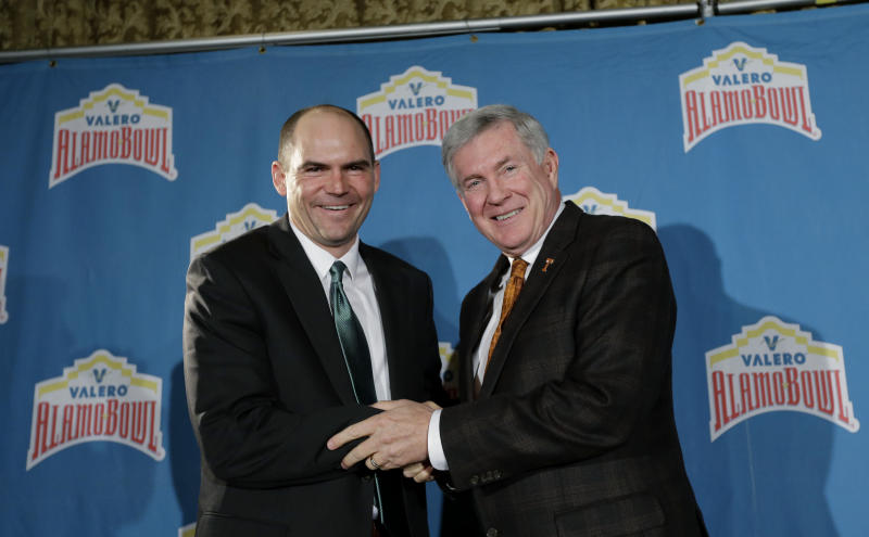 Oregon coach Mark Helfrich, left, and Texas coach Mack Brown, right, pose for a photo following a Valero Alamo Bowl news conference, Thursday, Dec. 12, 2013, in San Antonio. Texas and Oregon will play in the NCAA college football game Dec. 30. (AP Photo/Eric Gay)