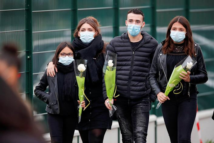Image: People bring flowers to the Bois d'Aulne college after the attack in the Paris suburb of Conflans St Honorine (CHARLES PLATIAU / Reuters)