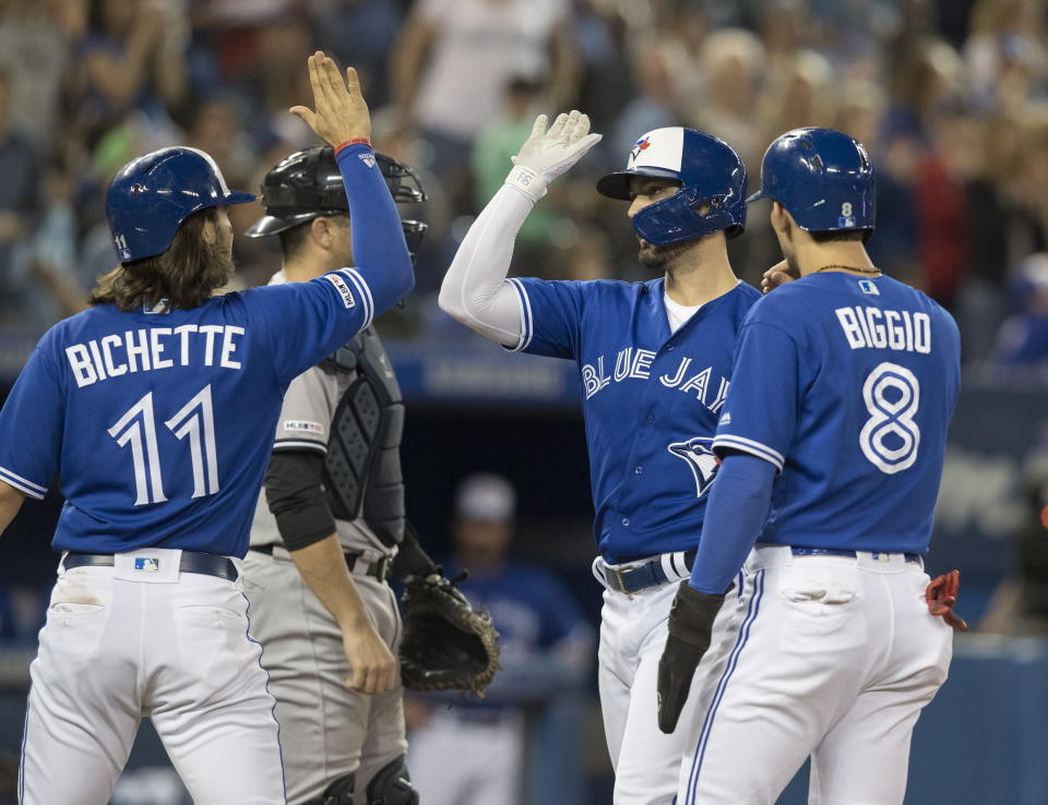 Toronto Blue Jays Randal Grichuk is met at home plate by teammates Cavan Biggio and Bo Bichette after hitting a three-run home run against the New York Yankees in the fifth inning of a baseball game in Toronto, Sunday, Sept. 15, 2019. (Fred Thornhill/The Canadian Press via AP)
