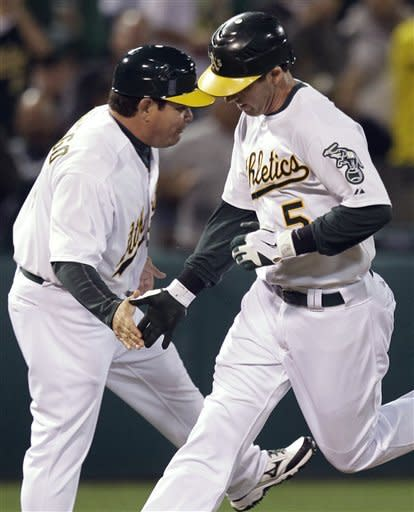 Oakland Athletics' Stephen Drew, right, is congratulated by third base coach Mike Gallego after hitting a home run off Seattle Mariners' Blake Bevan in the third inning of a baseball game Friday, Sept. 28, 2012, in Oakland, Calif. (AP Photo/Ben Margot)