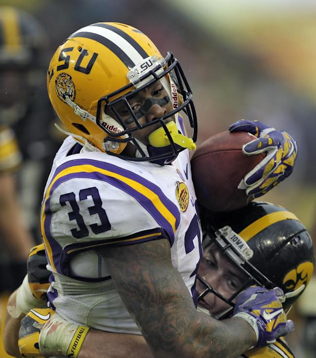 LSU running back Jeremy Hill (33) carries Iowa linebacker James Morris (44) into the end zone to score on a 14-yard touchdown run during the second quarter of the Outback Bowl NCAA college football game Wednesday, Jan. 1, 2014, in Tampa, Fla. (AP Photo/Chris O'Meara)