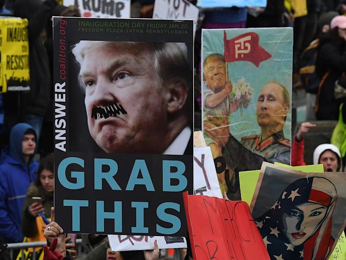 <p>Protesters wave signs at President Donald Trump and first lady Melania Trump as they drive the inaugural parade route on Pennsylvania Ave. in Washington, Jan. 20, 2017. (Photo: Mark Ralston/AFP/Getty Images) </p>