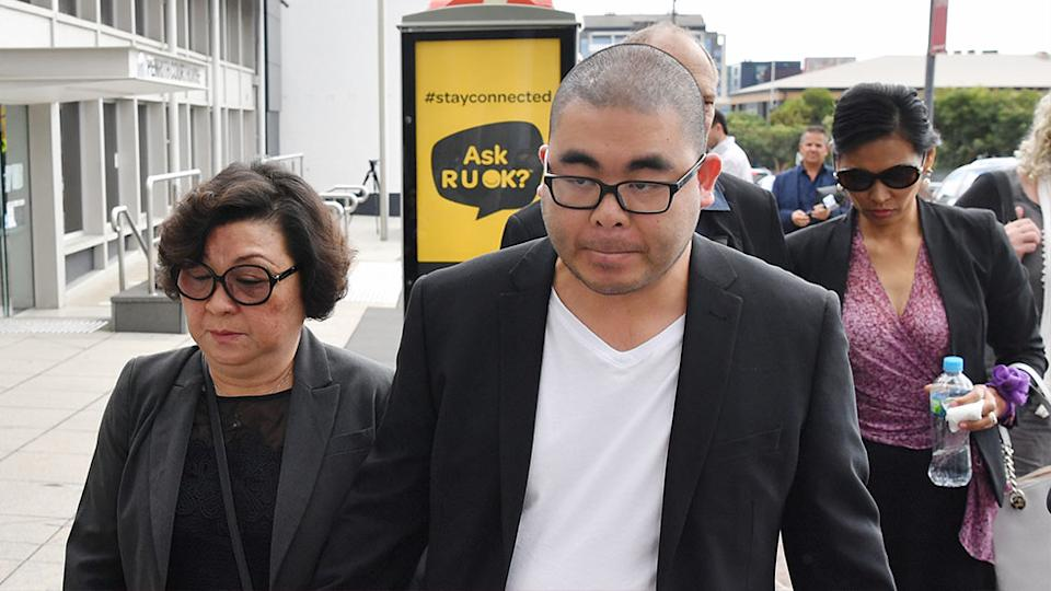 Bronko Hoang (centre), the husband of Katherine Hoang, leaves with family and supporters at the Penrith District Court. Source: AAP