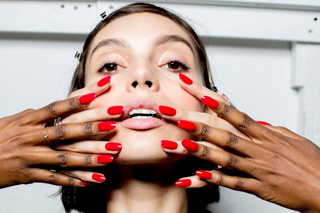 <p>Manicurist Holly Falcone outfitted shaped the model's almond-shaped nails with a combination of Orly Breathable Treatment and a true red crème color called Love My Nails.(Photo: Orly Products) </p>