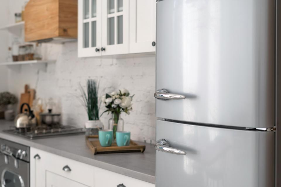Selective focus on new refrigerator against wooden furniture with cabinets in modern kitchen. Concept of apartment with white interior