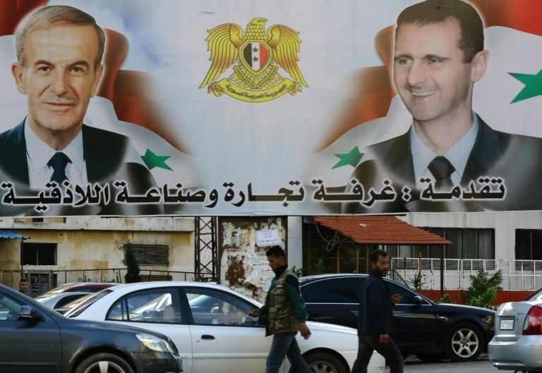 A billboard shows pictures of Syrian President Bashar al-Assad (R) and his late father former president Hafez in the coastal city of Latakia, a stronghold of his Alawite sect and Shiites