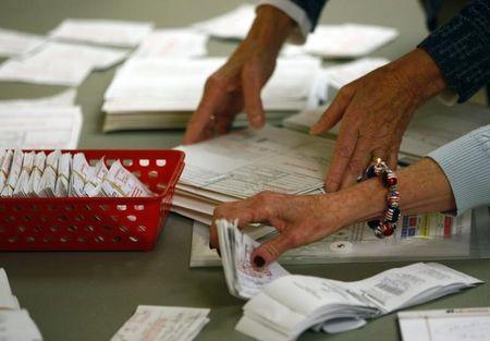 Poll workers review voter authorization forms and provisional ballots after the polls closed at a church during the U.S. presidential election in Charlotte, North Carolina