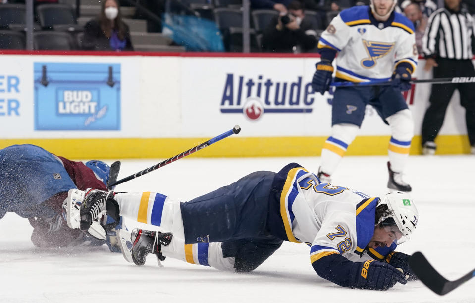 St. Louis Blues defenseman Justin Faulk, right, falls to the ice after he was hit by Colorado Avalanche center Nazem Kadri during the third period of Game 2 of an NHL hockey Stanley Cup first-round playoff series Wednesday, May 19, 2021, in Denver. Kadri was removed from the game for the hit. Colorado won 6-3. (AP Photo/David Zalubowski)