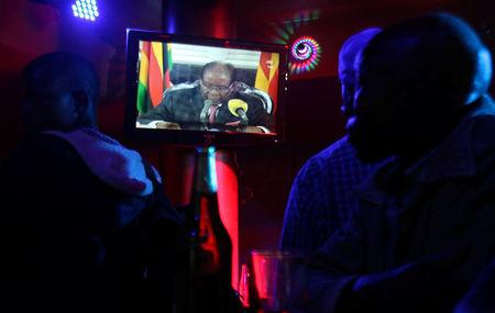 People watch as Zimbabwean President Robert Mugabe addresses the nation on television, at a bar in Harare