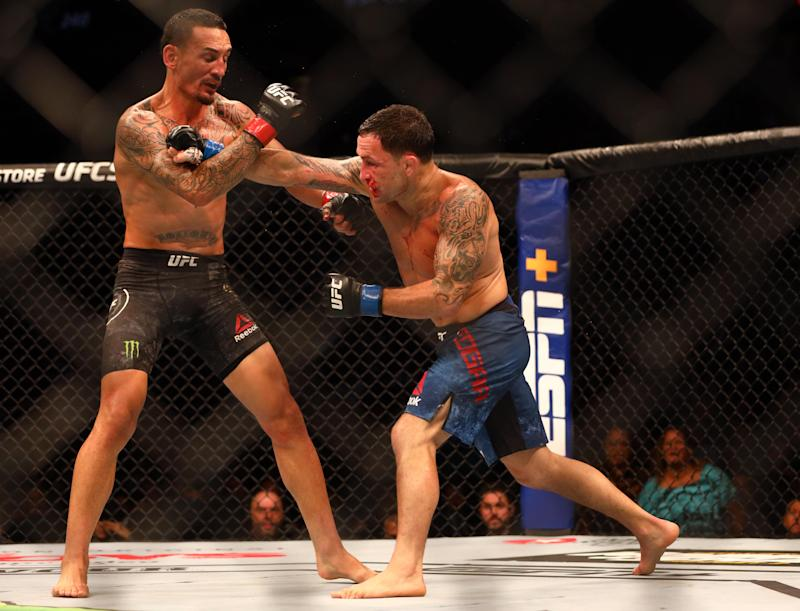 Jul 27, 2019; Edmonton, Alberta, Canada; Max Holloway (red gloves) and Frankie Edgar (blue gloves) during UFC 240 at Rogers Place. Mandatory Credit: Sergei Belski-USA TODAY Sports