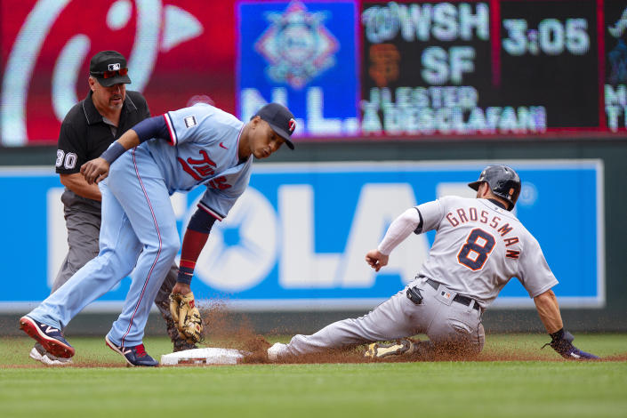 Minnesota Twins shortstop Jorge Polanco (11) is late on a tag of Detroit Tigers left fielder Robbie Grossman (8) slides safely into second base in the first inning of a baseball game, Saturday, July 10, 2021, in Minneapolis. (AP Photo/Andy Clayton-King)